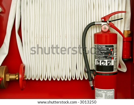 powder fire extinguisher and water hose, red and white - stock photo