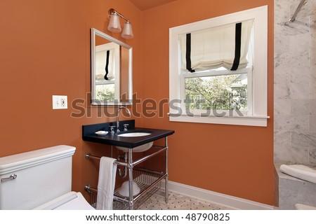 Powder room in suburban home with orange walls - stock photo
