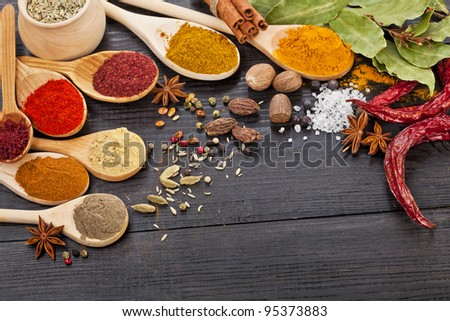 Powder spices assortment on spoons in black wooden table background - stock photo