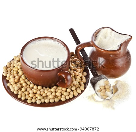powdered milk drink in clay pitcher and cup, spoon , soy beans , on white background - stock photo