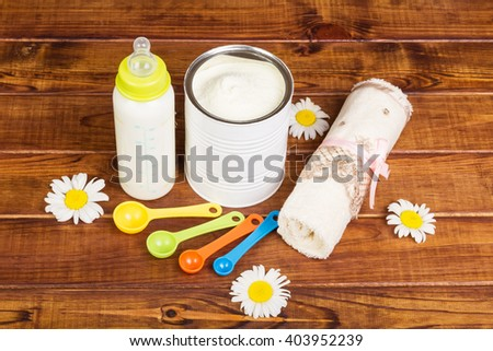 Powdered milk, with a mixture of bottle and measuring spoons on a background of light wood.