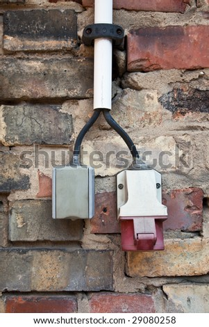 power and high-power current on brick wall - stock photo
