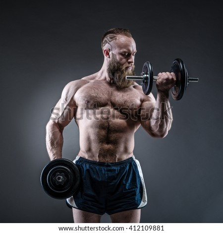 Power athletic bearded man in training pumping up muscles with dumbbell. Strong bodybuilder with six pack, perfect abs, shoulders, biceps, triceps and chest.  - stock photo