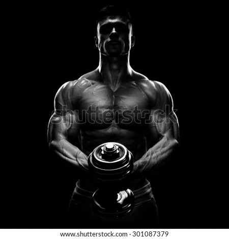 Power athletic man pumping up muscles with dumbbell. Confident young fitness man with strong core muscles, power hands and clenched fists. Silhouette of a bodybuilder. Black and white photo - stock photo