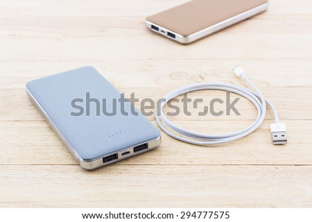 Power bank and USB cable for smartphone on wood background. - stock photo