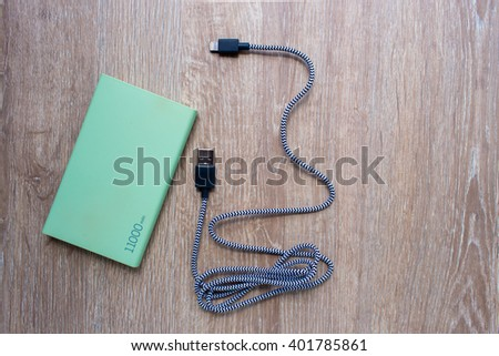 Power bank and usb cable on wooden background - stock photo