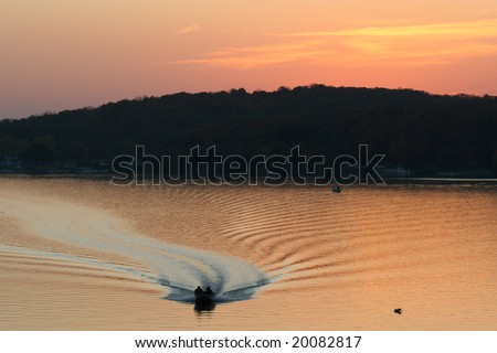 Power Boat coming back with a sunset background - stock photo