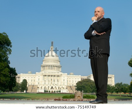 Power broker type in a suit, hand on chin standing in front of the U.S. Captiol building, downtown Washington, DC, USA. - stock photo