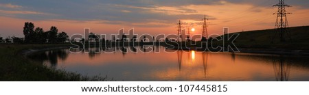 power cable line. sunset on the river - stock photo
