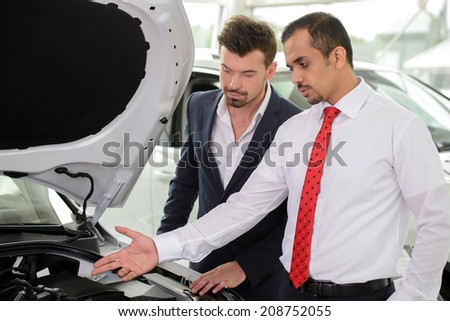 Power engine. Handsome young salesman showing all the car features to the customer - stock photo