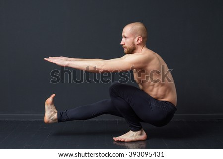 Power fitness. Young man with naked torso is doing a  pistol exercise, gray background - stock photo