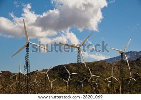 power generating wind turbines against blue sky - stock photo