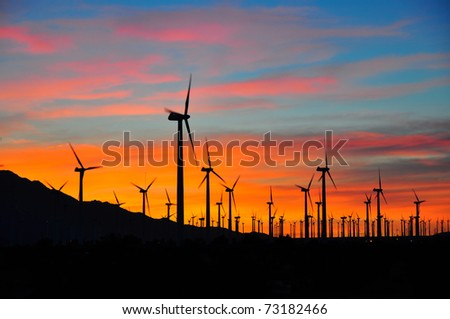 Power generating windmills against sunset - stock photo