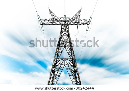 power grid pylon against blue cloudy sky with visible motion blur - stock photo