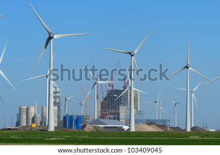 Power industry: new power station being build between wind turbines in the Eemshaven, Holland. - stock photo