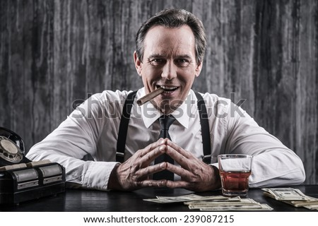Power is in his hands. Smiling senior man in shirt and suspenders sitting at the table and smoking cigar while lots of money laying near him  - stock photo