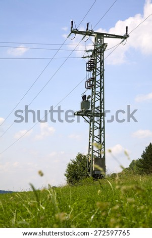 Power line and a electricity pylon with transformer, summer, Saarland/Germany - stock photo