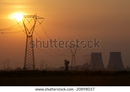 Power line of a nuclear power station; sunset. - stock photo