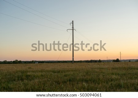 Power line on meadow at sunset. Bulatovo, Kaluzhsky region, Russia.