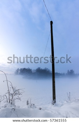 Power line or telephone line to a remote house in a foggy winter evening - stock photo