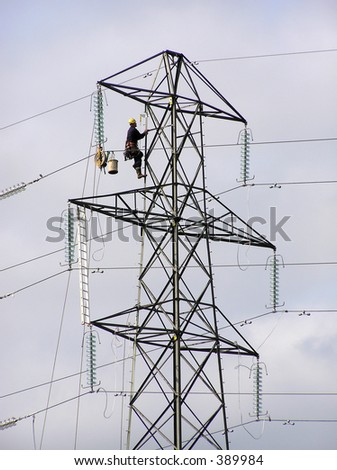 Power lineman climbing electricity pylon - stock photo