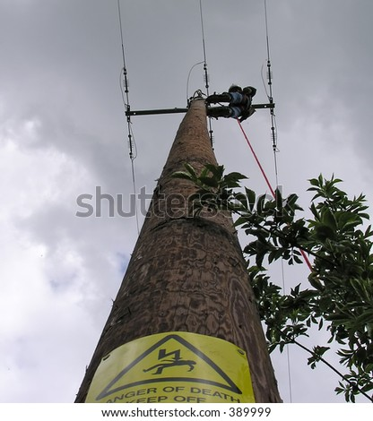 Power lineman up pole - stock photo