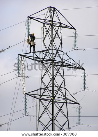Power lineman up pylon tower - stock photo