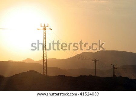 Power lines and array of electric pylons in Judea desert - stock photo