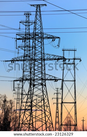 Power lines and electric pylons against a blue sky