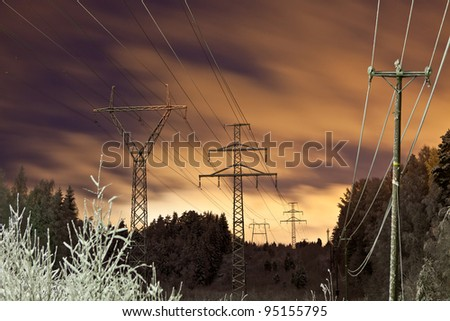 Power lines and yellow clouds at night - stock photo