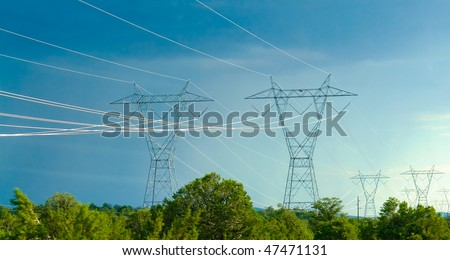 Power Lines Glowing In The Sun against blue sky and green trees.