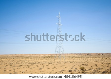 Power lines in rocky desert at the beginning of Sahara in the middle of Tunisia. - stock photo