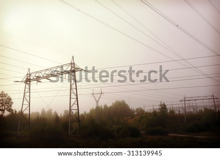 Power lines on a foggy and cold morning. Image has a vintage effect applied and also some grain is added.