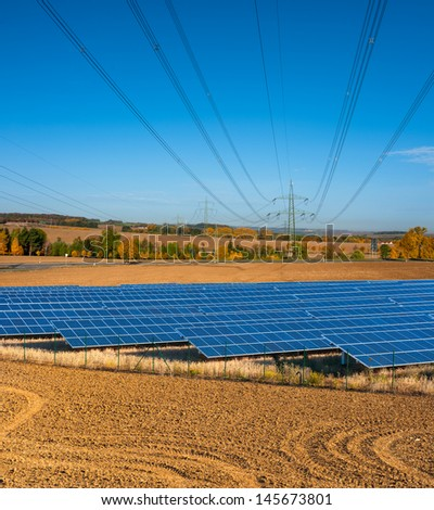 Power lines run above solar power station - stock photo