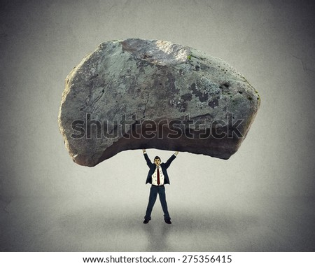 Power of leadership with the ability to inspire as a businessman lifting up a huge boulder removing a large obstacle and leading by example as a business concept of success and determination.  - stock photo