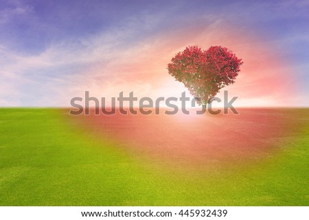 Power of love, red color tree in heart shape symbol,  representing romantic love spreading red color to grass field and blue sky, Valentine's Day holiday concept. - stock photo