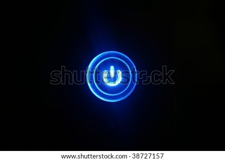 Power on - Blue glowing button on black background - stock photo