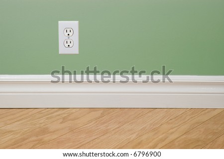 Power outlet on green wall with hardwood flooring - stock photo