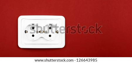 Power outlet on red wall - stock photo