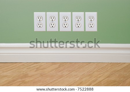 Power outlets on green wall (energy crisis concept) - stock photo