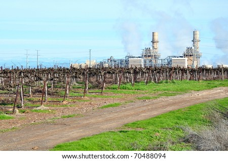 Power plant against blue sky with vineyard in foreground