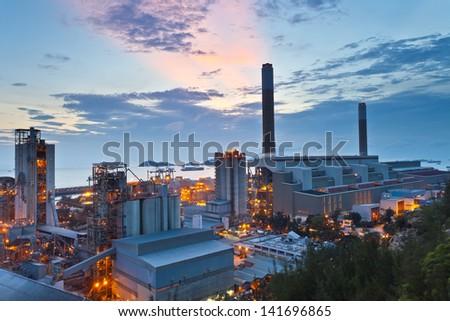 Power plant at sunset along coast - stock photo