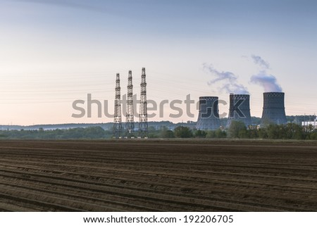 Power plant cooling towers with high supports of electricity transmissions - stock photo
