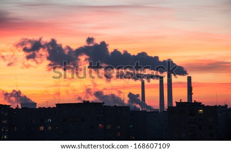 Power Plant emissions seen above residential blocks from a city during sunrise. Environmental pollution. Factory pipe polluting air.  - stock photo