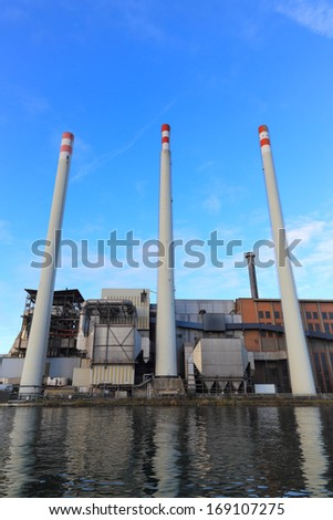 Power plant industry along the river with tall chimney, water reflections. Vertical, nobody