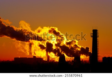 power plant smokestacks at sunset