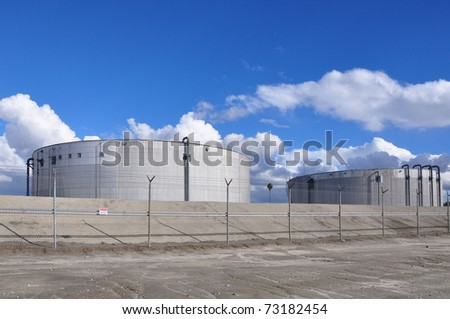 Power plant storage towers against cloudy blue sky - stock photo