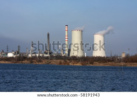 power plant view and small lake with dark blue water - stock photo