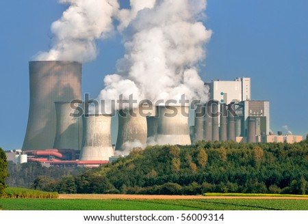 Power plant with huge cooling towers, in contrast to its nice surrounding area - stock photo