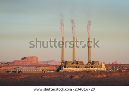 power plant with large smoke stacks and a yellowish haze in the background, concept for air pollution - stock photo